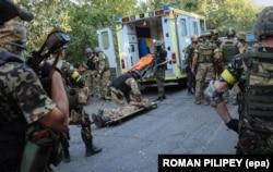 Украинские военные спасают раненого бойца во время боев под Иловайском, 10 августа 2014