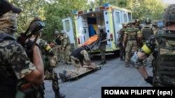 Українські бійці рятують товариша, пораненого під час бою з російськими гібридними силами поблизу Іловайська, 10 серпня 2014 року