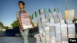 Тегеран кітап жәрмеңкесінде кітап көтеріп бара жатқан жігіт.