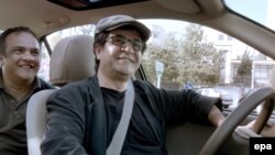 Iranian director Jafar Panahi (right) in a still from his film Taxi