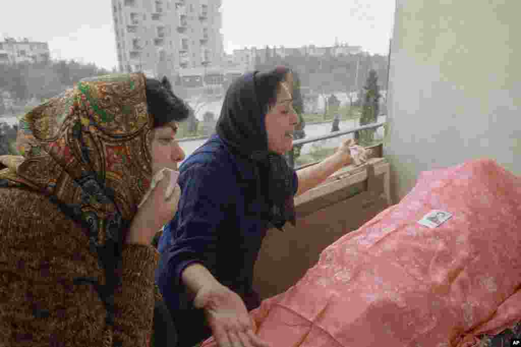Two Azerbaijani women overcome with grief next to the body of a relative in Baku on January 28.