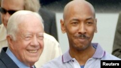 Former U.S. President Jimmy Carter (left) poses with Aijalon Mahli Gomes at Pyongyang airport.