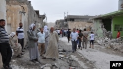 People inspect damage at the site of two car bomb blasts in the Iraq town of Tuz Khurmatu on May 21.