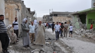 People inspect damage at the site of two car bomb blasts in the Iraqi town of Tuz Khormato on May 21.
