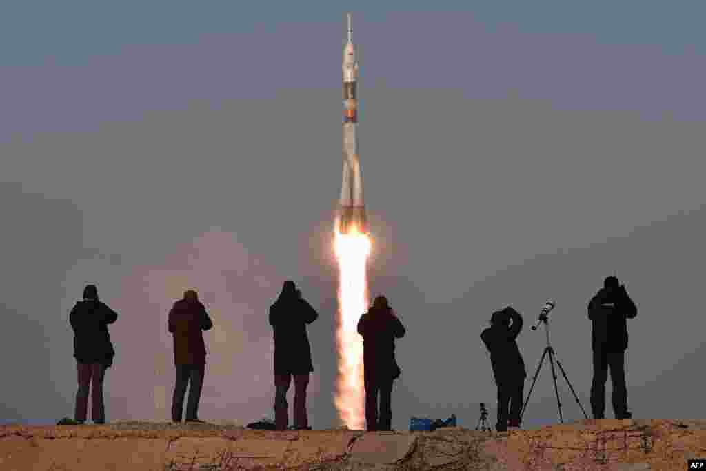 Photographers take pictures as Russia's Soyuz TMA-19M spacecraft carrying British stronaut Tim Peake, Russian cosmonaut Yuri Malenchenko, and U.S. astronaut Tim Kopra blasts off from Kazakhstan on December 15. (AFP/Kirill Kudryavtsev)
