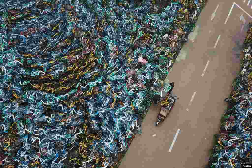 Urban-management officers transport a bicycle next to piled-up bicycles of bike-sharing services in Hefei in China's Anhui Province. (Reuters)