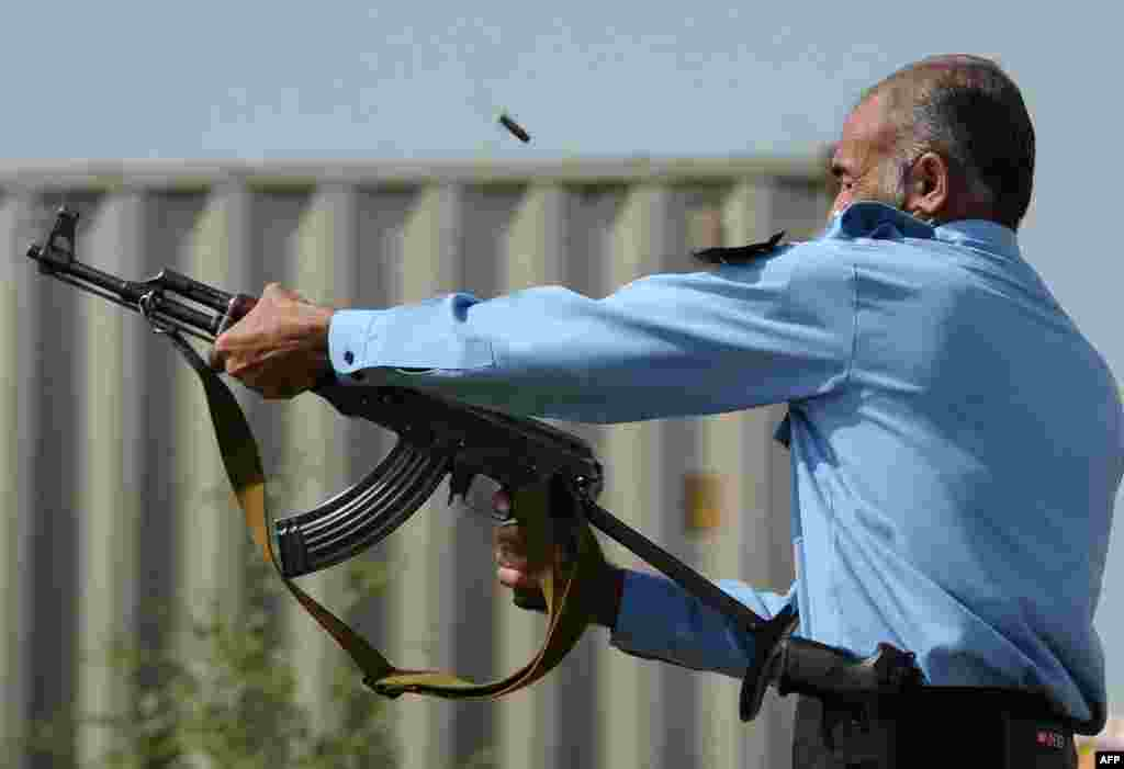 A Pakistani policeman fires an automatic weapon at demonstrators.