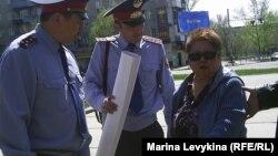 """Полиция пытается увести активиста оппозиции Фатиму Касенову с митинга """"Несогласных"""". Семей, 28 апреля 2012 года."""
