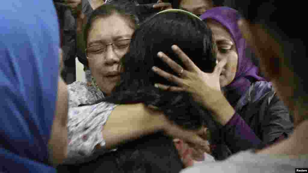Relatives of a passenger of the missing Sukhoi aircraft grieve as the ill-fated plane's passenger list is checked at Halim Perdana Kusuma Airport in Jakarta.