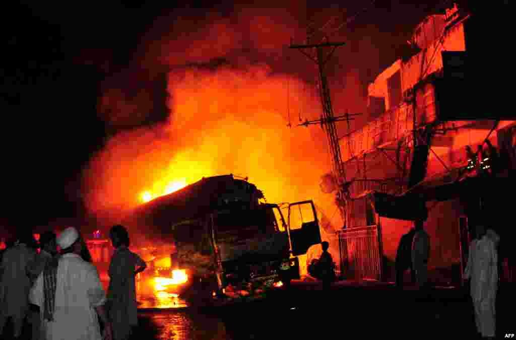 Men gather around a burning NATO oil tanker near a market in the Pakistani city of Peshawar on July 16. According to security officials, three people were killed and 16 others wounded when militants blew up a NATO oil tanker and opened fire on another in Pakistan's troubled northwest.Photo by A. Majeed for AFP
