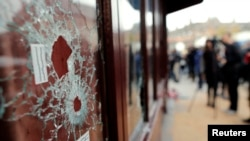 След от пуль в окне ресторана на месте теракта в Париже. 14 ноября 2015 года.