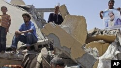People stand in the rubble of a home in the Libyan city of Zliten that was reportedly destroyed by a NATO bomb in August 2011.