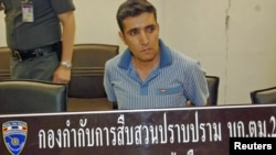 Suspect Mohammad Hazaei sits behind Thai immigration police sign after he was arrested at Suvarnabhumi Airport in Bangkok on February 14.