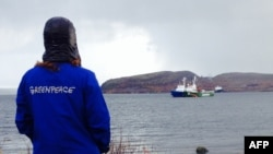 "A Greenpeace activist looks at the ""Arctic Sunrise"" protest ship moored next to a Russian Coast Guard vessel near Murmansk."