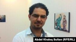 الفنان جواد مراد أمام لوحة من اعماله