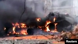A tank burns, allegedly after being attacked by insurgents from the Free Syrian Army, in the city of Homs on January 12.