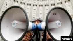 Участник акции в поддержку евроинтеграции Украины стоит у здания правительства страны. Киев, 25 ноября 2013 года.
