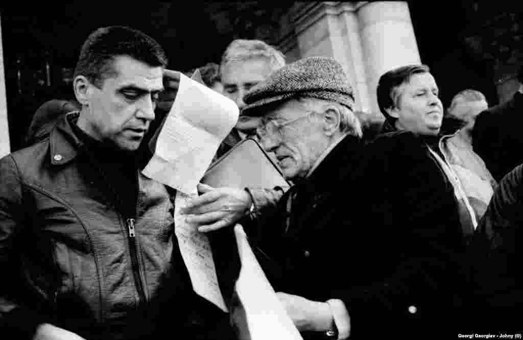 """Малко преди думата да вземе Петър Гогов (вляво, с коженото яке), на площада пее Ангел Ангелов - Джендема - един от любимите изпълнители на тогавашния ъндъргаунд. В неговата песен """"Край на живота от самото начало"""" се съдържа и следния стих: """"Вашите кожи ще съхнат по стените"""". В изказването си Гогов призовава: """"... и никакви кожи по стените!"""" Впоследствие думите му се изопачават дотам, че му е приписан и призив да се бесят комунистите. След известно време Джендема спира да изпълнява песента. Петър Гогов, който по-рано е лежал в затвора, остава встрани от обществения живот."""