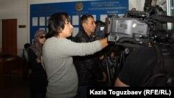 Журналисты и жена подсудимого Саяна Хайрова Шынар Бисенбаева (крайняя слева) в фойе здания Алмалинского районного суда. Алматы, 27 сентября 2013 года.