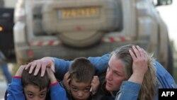 یک مادر اسرائیلی با دو فرزندش در مقابل یک حمله راکتی حماس پناه گرفته است.
