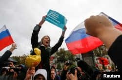 "Supporters of Russian opposition leader Aleksei Navalny attend a rally in Moscow. The sign reads: ""Freedom of elections, freedom to Navalny"""