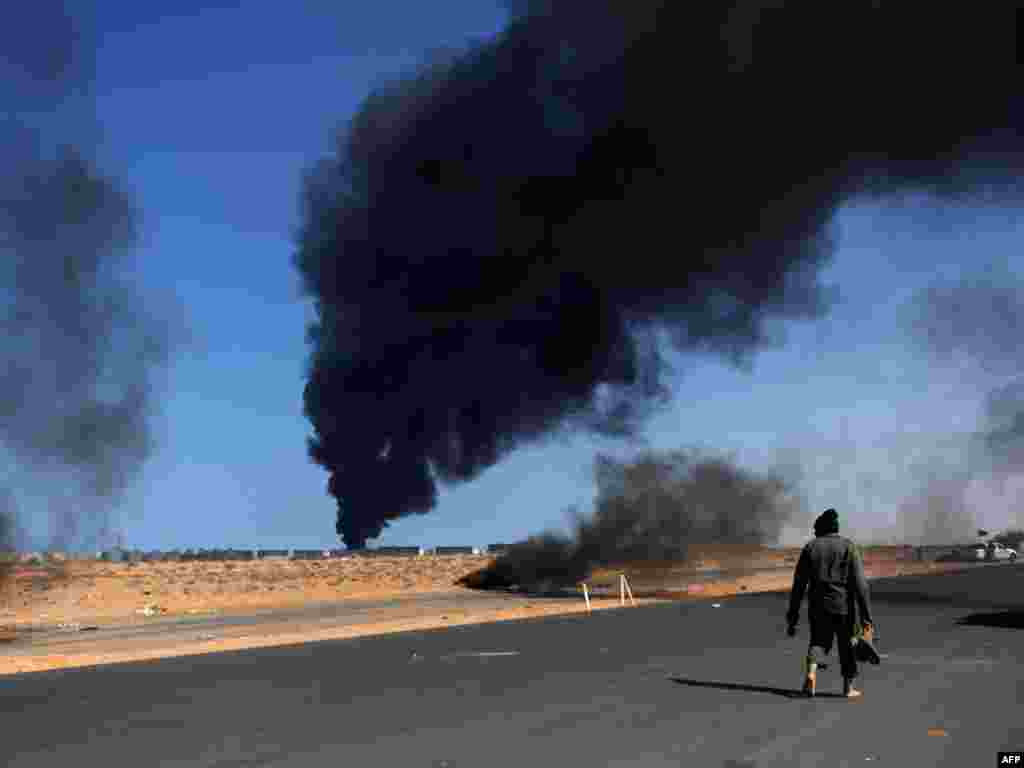 A Libyan rebel fighter walks barefoot near burning tires as smoke rises from an oil refinery storage tank near the oil port of Ras Lanuf. Photo by Roberto Schmidt for AFP