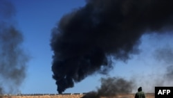A rebel fighter walks past as smoke rises from an oil refinery storage tank near Ras Lanouf.