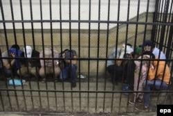 """Группа египетских мужчин в клетке в зале суда, задержанная за """"непристойное поведение"""". 1 ноября 2014 года"""