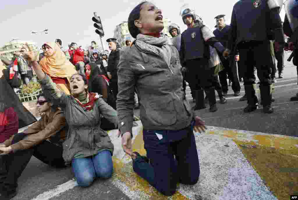 Demonstrators protest near police on January 25, 2011, to demand the ouster of Mubarak and call for reforms.