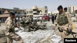 Iraqi soldiers survey the site of one of the bomb attacks in Karbala on March 29.