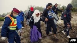 Венгрияның Хорватиямен шекарасы маңындағы мигранттар мен венгр полициясы қызметкері. 16 қазан 2015 жыл.