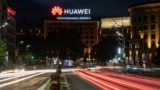 Cars drive past a Huawei logo on a building in central Belgrade.