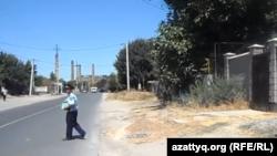 Полицейский стоит на месте взрыва в микрорайоне Онтустик города Шымкента. 14 августа 2015 года.