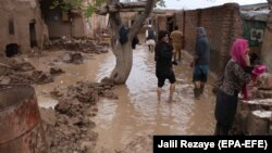 Afghans survey their damaged houses after seasonal floods in Herat on March 29.