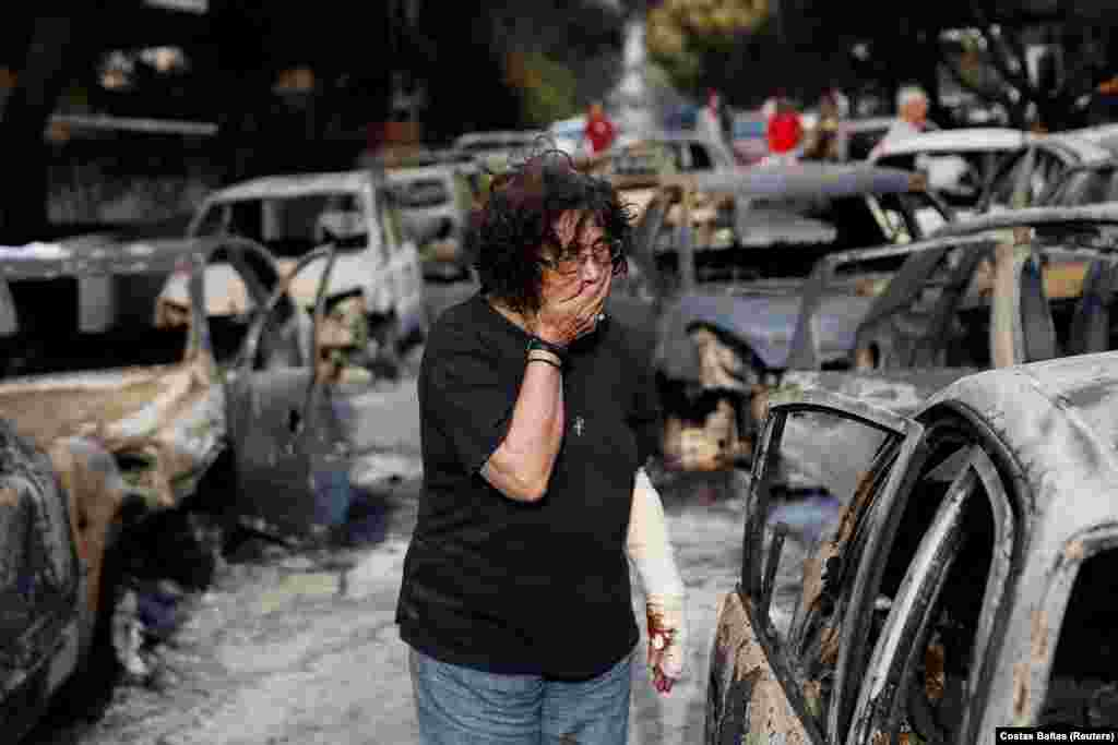 A woman reacts as she tries to find her dog following a wildfire in the village of Mati. At least 60 people have died in wildfires near Athens in the country's deadliest blazes in more than a decade. (Reuters/Costas Baltas)