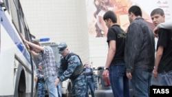 Сотрудники полиции проводят проверку документов и личный досмотр мигрантов на рынке «Теплый стан» в Москве.