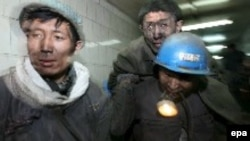 A rescue worker carries a trapped miner out of a mine in China's Heilongjiang Province following a November 2005 explosion.