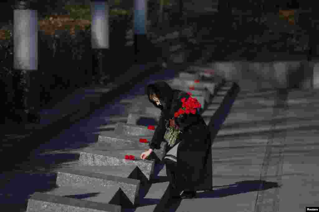 A woman lays flowers during a wreath laying ceremony at the Unknown Soldier's Tomb in Kyiv on October 28 as Ukraine commemorates the 70th anniversary of the liberation of the city from Nazi rule in 1944. (Reuters/Gleb Garanich)