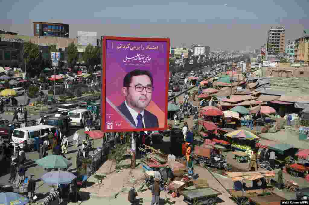 Afghan commuters and pedestrians are seen along a road in Kabul featuring a billboard of parliamentary candidate Haji Hafizullah Jalili. Campaigning for Afghanistan's long-delayed parliamentary elections kicked off on September 28. (AFP/Wakil Kohsar)