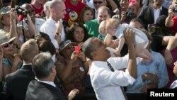 Presidenti amerikan, Barack Obama, mban një foshnje pesë-muajshe gjatë një tubimi elektoral në Nevada.