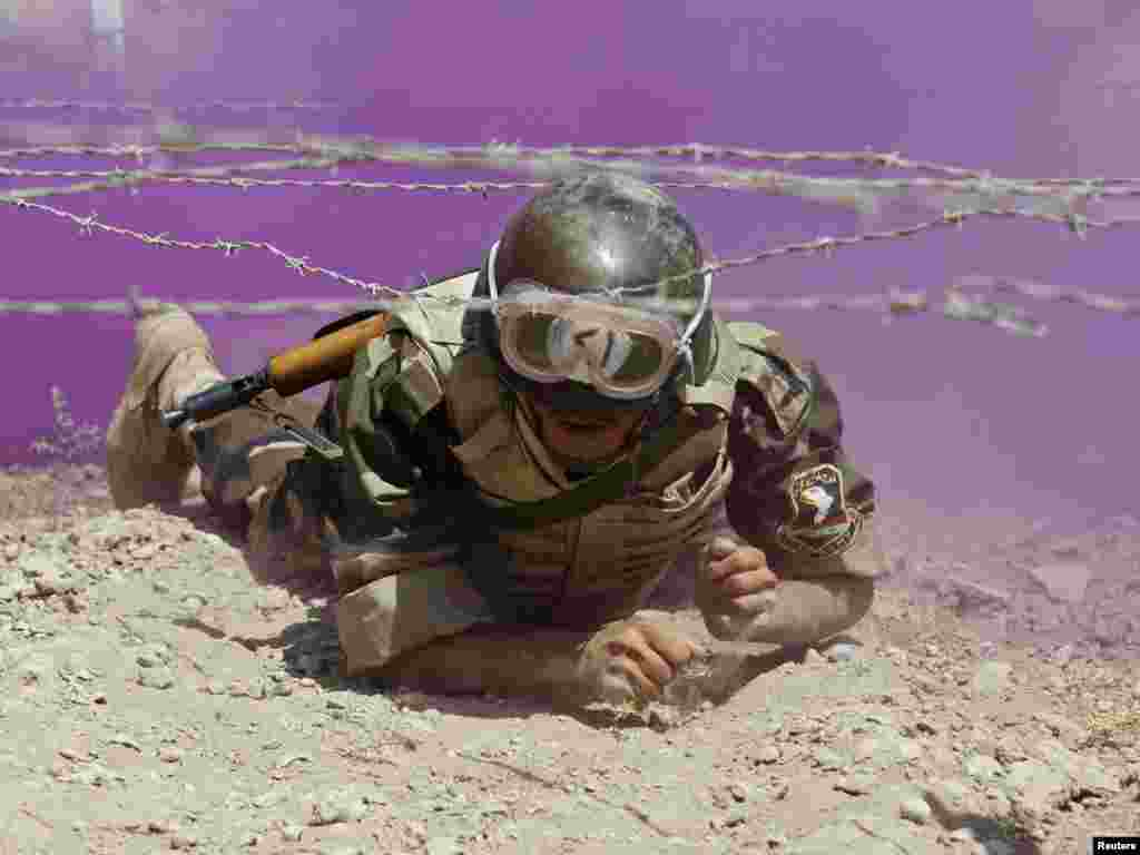An Iraqi soldier crawls through colored smoke and barbed wire during a training course at an Iraqi military base south of Baghdad on August 30. With the official end to U.S. combat operations in Iraq on August 31, the Pentagon hopes the focus will shift to training Iraqi troops to maintain security.Photo by Saad Shalash for Reuters