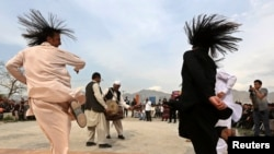 "Afghan men perform a traditional ""Attan""."