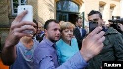 Мігранти в Німеччині фотографуються з канцлером Анґелою Меркель, 10 вересня 2015 року
