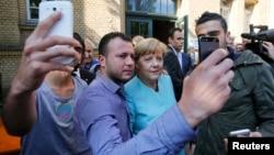 Берлиндегі босқындар орталығында канцлері Ангела Меркельмен (ортада) суретке түсіп тұрған мигранттар. Германия, қыркүйек 2015 жыл.