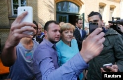 Refugees from Syria and Iraq take selfies with German Chancellor Angela Merkel outside a refugee camp near the Federal Office for Migration and Refugees in Berlin in September.