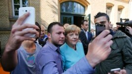Syrian and Iraqi migrants take selfies with German Chancellor Angela Merkel in Berlin on September 10, 2015.