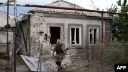 Український військовослужбовець біля зруйнованого внаслідок обстрілу будинку. Селище Сартана. 17 серпня 2015 року