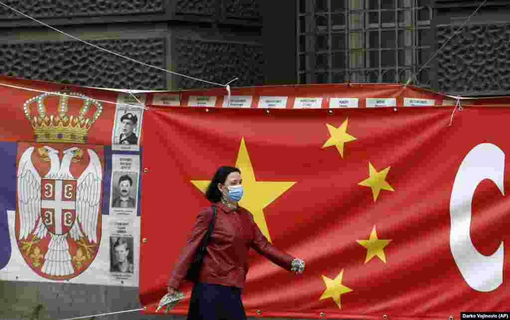 """O femeie trece pe lângă afișe gigantice care leagă steagurile chineze și sârbe la Belgrad. Zoric spune că Rusiași China sunt """"foarte prezente"""" în Serbia și semnalele de acest tip ar putea fi o modalitate de a sugera UE că țara are și alte opțiuni de aliniere geopolitică."""