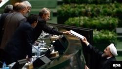 Иран президенті Хассан Роухани (оң жақта) парламент спикері Али Ларжаниге бюджет жобасын беріп жатыр. Тегеран, 17 қаңтар 2016 жыл.