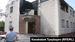 Өртенген үйдің ауласында тұрған полицей. Алматы облысы, 17 шілде 2012 жыл.